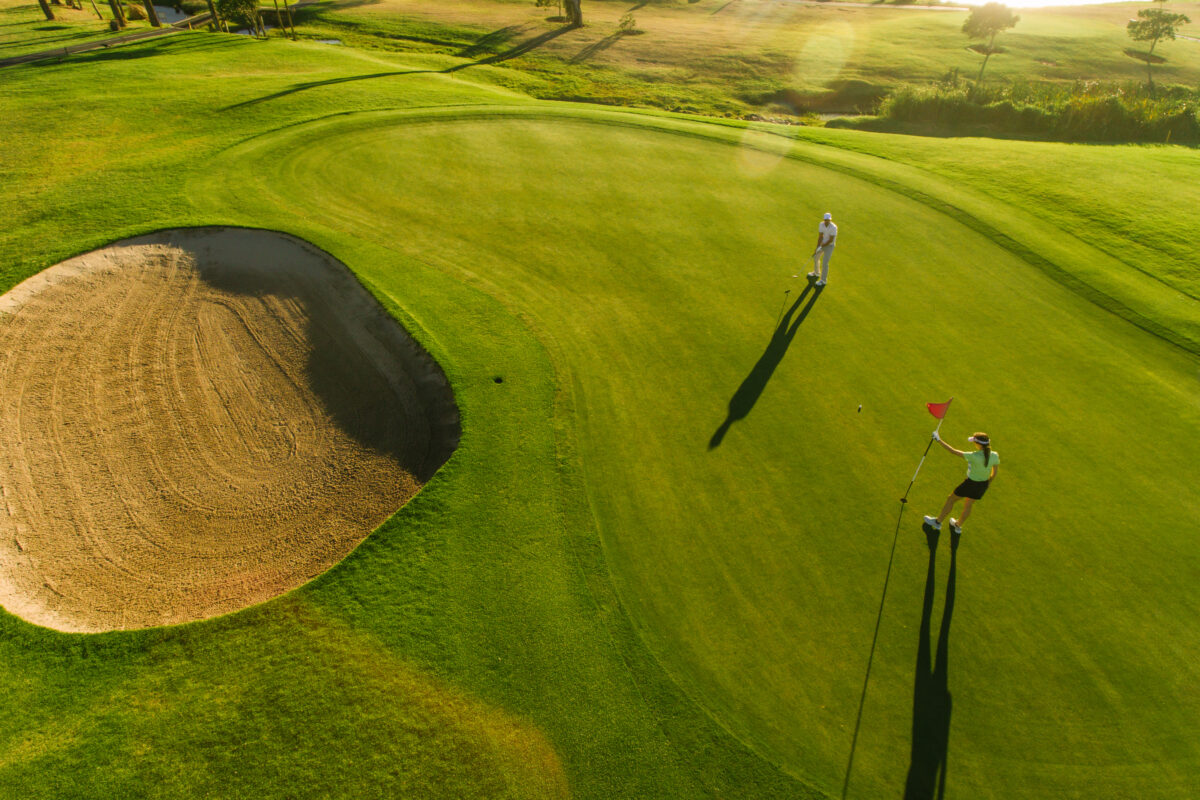 Aerial view of golf player in fringe golf course field