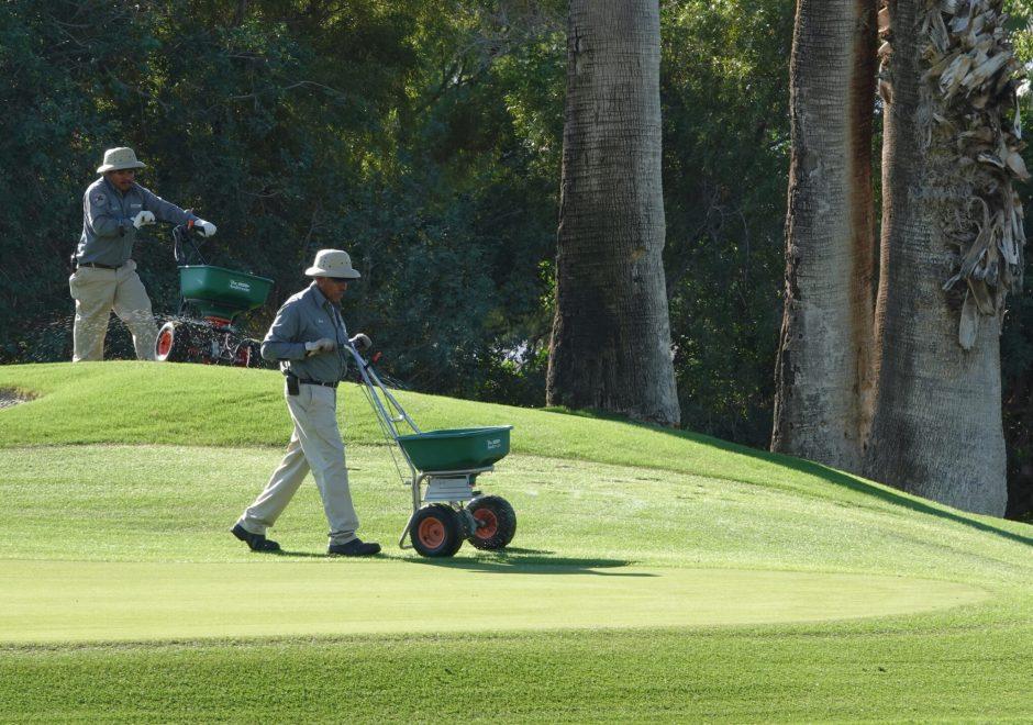 Two men applying fertilizer